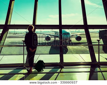 Back View Of Young Tourist Woman Looking Out Of Window In Airport Lounge.