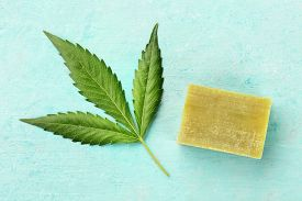 A Cannabis Leaf With Homemade Hemp Soap Bar, Shot From Above On A Teal Blue Background With A Place