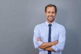 Happy smiling businessman leaning on grey wall with copy space. Handsome mature business man isolated on gray background. Portrait of a satisfied formal man with arms crossed looking at camera.