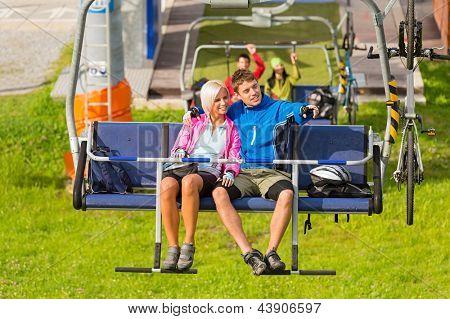 Couple on chair lift enjoying landscape