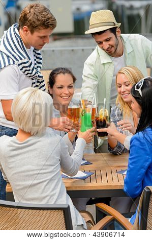 Group of cheerful young people toasting with cocktails outdoor terrace