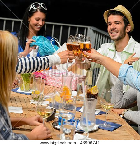 Young people celebrating birthday toasting with beer outdoors