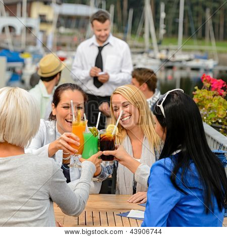 Women celebrating with cocktails at harbor restaurant