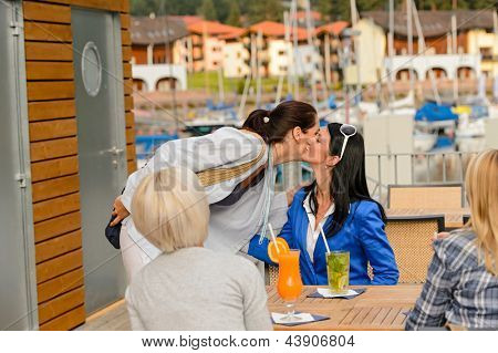 Woman saying goodbye to her friends at outdoor restaurant terrace