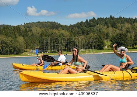 Friends enjoying summertime kayaking on river holiday free time