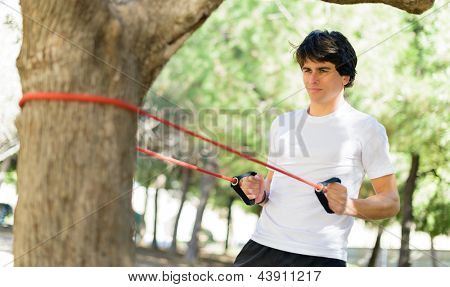Young Man Exercising With Stretch Band; Outdoors