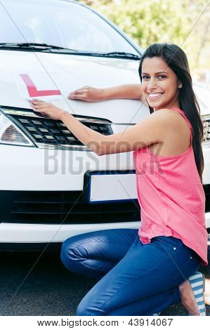 Confident learner driver girl proud of passing her test with car
