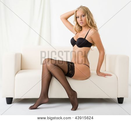 attractive young woman in black lingerie on a sofa