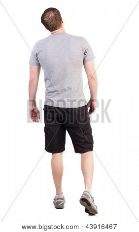 Back view walking handsome man. Sports-dressed young man moves. going young guy. Rear view people collection.  backside view person. Isolated over white. broad sporsmen in long shorts are looking up