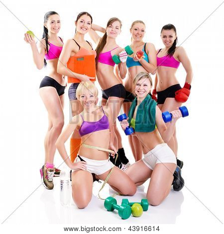 Group of fitness girls holding measuring tape, dumbbells, scales, boxing gloves and apples. Portrait of sport young women with perfect bodies, studio shot over white