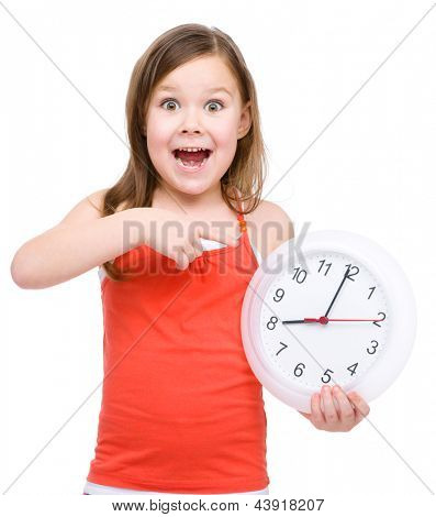 Little girl is holding big clock and pointing at it, isolated over white