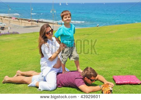 Beautiful four year old boy having fun playing with his uncle and aunt on a green grassy lawn. A young pregnant woman smiling