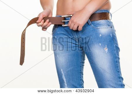 a young woman has her tighten our belts. image symbolizing debt, sovereign debt and personal bankruptcy