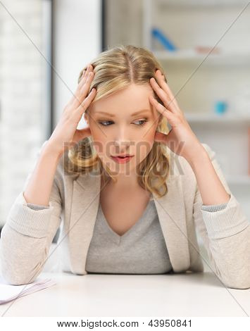 indoor picture of bored and tired woman behind the table