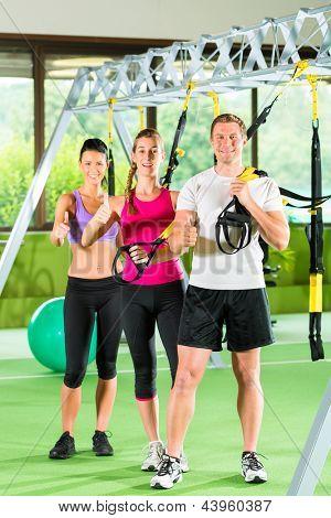 Gruppe von Menschen trainieren mit Schlingentrainer oder Suspension trainer in Fitnessstudio