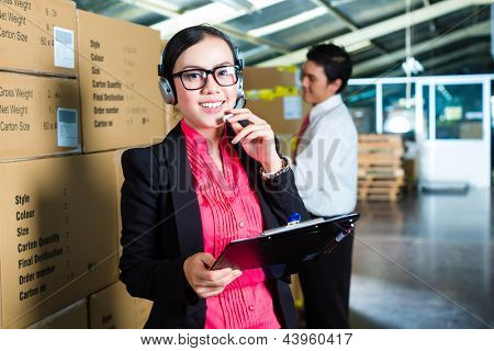 Young woman in a suit with headset in a warehouse, she is from the Customer Service, a coworker standing in background