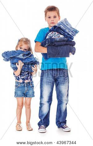 School aged boy and preschool girl holding jeans clothing in hands