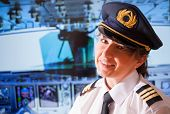 Beautiful woman pilot wearing uniform with epauletes, hat with golden wings sitting inside airliner with visible cockpit during flight. poster