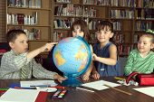Four Elementary school students study geography in library poster