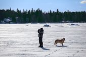 Man with dog looking at binocular and standing on frozen lake poster