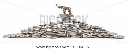 Pyramid made with many coins with lucky elephant on the top