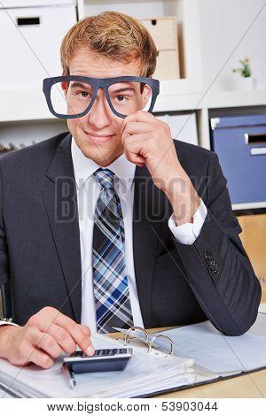 Smiling business man holding nerd glasses in front of his face in the office