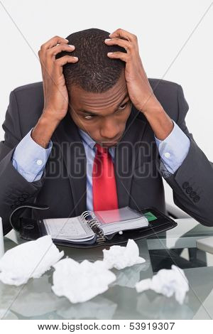 Frustrated young Afro businessman with head in hands at desk against white background