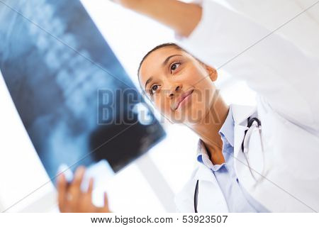 healt and medicine concept - smiling female doctor studying x-ray poster