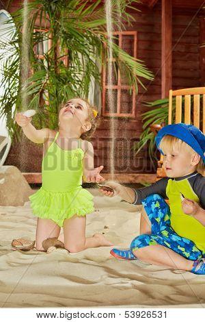 Children catch trickles of sand with halfs of seashells