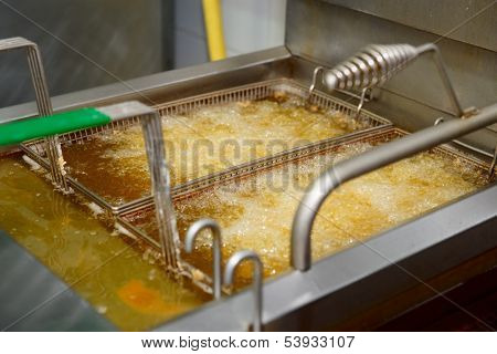 Deep fryer with boiling oil on fast food kitchen