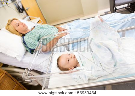 Cute newborn babygirl lying in bassinet with woman relaxing on hospital bed
