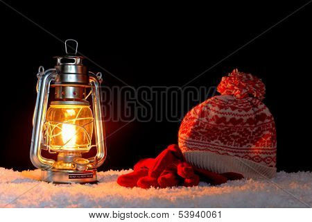 An oil filled lantern on snow with a bobble hat and gloves, black background.