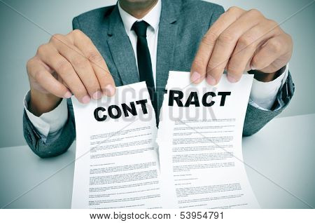 man wearing a suit sitting in a table ripping up a contract