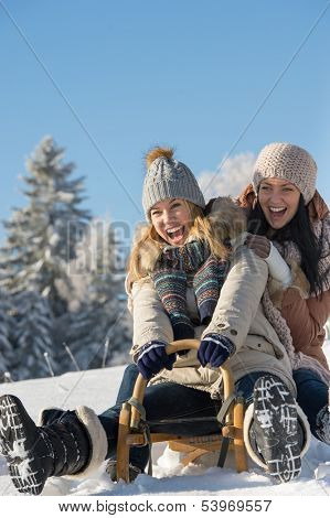 Laughing teenagers sledge downhill in wintertime enjoy snow