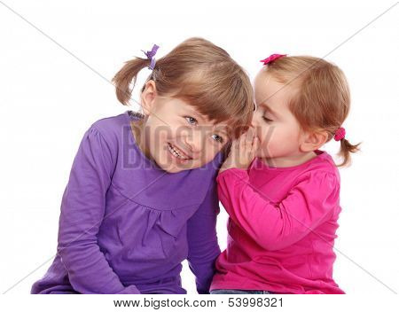 Two little girls telling secrets isolated on white background