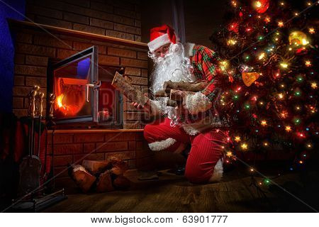 Santa Claus keep the fire in the stove near Christmas tree