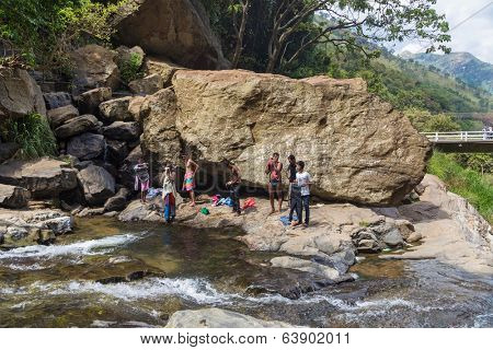 RAVANA FALLS, SRI LANKA - MARCH 2, 2014: Local men having fun at Ravana falls, popular sightseeing attraction and one of the widest falls in the country.