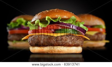 Classic burger on black background. Burger or hamburger in dramatic light. Modern burger or hamburger on black background. Homemade fast food concept. Mouthwatering hamburger. Delicious burger american fast food.