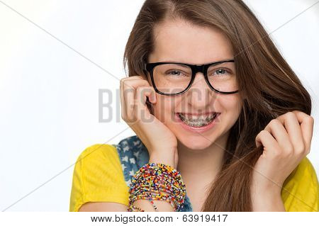 Cheerful girl with braces wearing geek glasses on white background