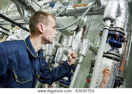 repairman engineer or inspector of fire engineering system or heating system with valve equipment in a boiler house