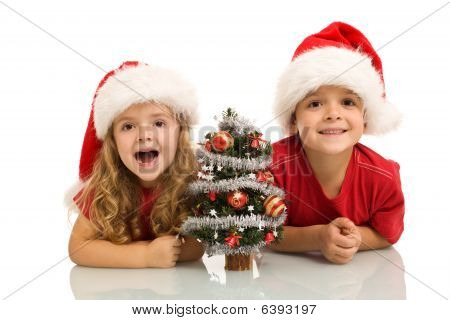 Kids With Small Decorated Tree At Christmas Time