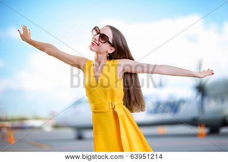 Young Woman Dressed In Yellow Dress Simulating Flight With Hands In Front Of Airplane