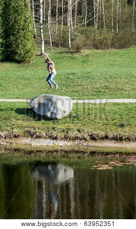 Young Woman Jumping On The Big Stone