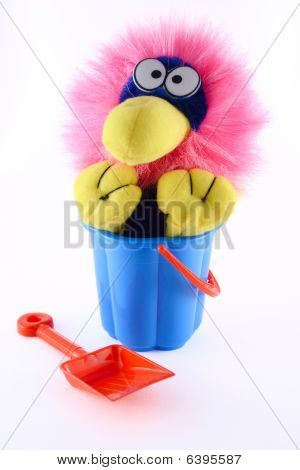Toy sitting in a dark blue bucket with a red scoop removed close up poster