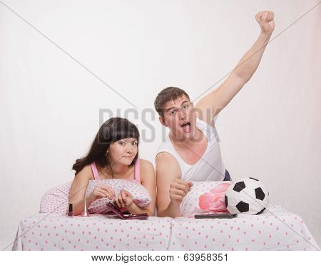 Beautiful girl has a manicure man watches soccer on TV.