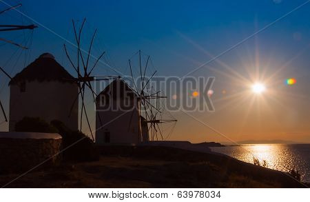 A Number Of Famous Windmills On The Island Of Mykonos At Sunset.