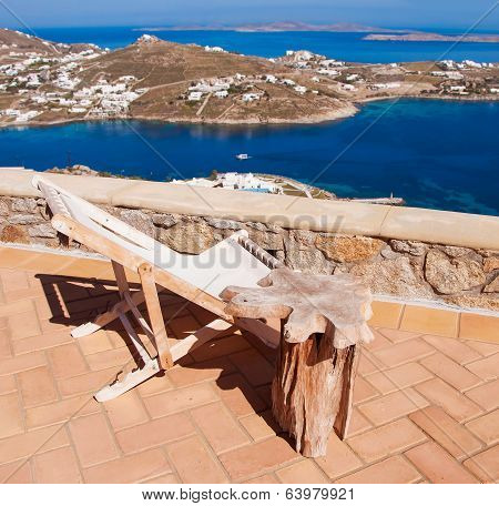 Rocking Chair And A Table On The Background Of The Sea And Islands...