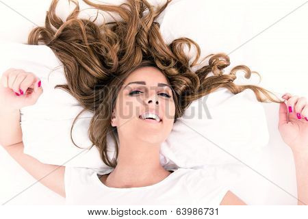 Portrait Of Young Woman Lying In Bed With Hair Spread Around