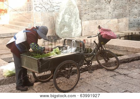 People Wash Vegetable Into A Tricycle In Dayan Old Town.