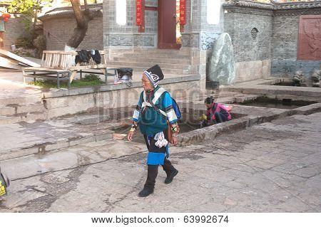 Traditional Chinese Nakhi Dressed Woman Walking Through Lijiang Old Town.